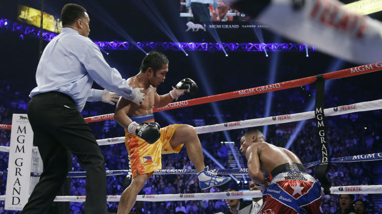 Michael Farenas, from the Philippines, center, sends Yuriorkis Gamboa, from Miami, Fla., to the canvas in the ninth round during their WBA interim super featherweight title fight as referee Tony Weeks looks on at left, Saturday, Dec. 8, 2012, in Las Vegas.(AP Photo/Julie Jacobson)