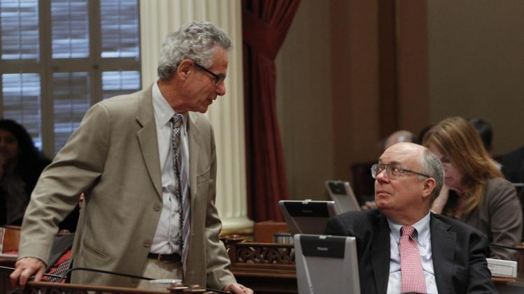 Sen. Alan Lowenthal, D-Long Beach, left, talks with Sen. Joe Simitian, D-Palo Alto, as the Senate debated a bill to authorize  about $4.5 billion in funding for a high-speed rail system, at the Capitol in Sacramento, Calif., Friday, July 6, 2012.   The bill, which would allow the state to begin selling $2.6 billion in voter -approved bonds, was approved by a 21-16 vote and now goes to Gov. Jerry Brown who has supports the measure.   Lowenthal and Simitian were two of three Democrats in the Senate to oppose the bill.(AP Photo/Rich Pedroncelli)