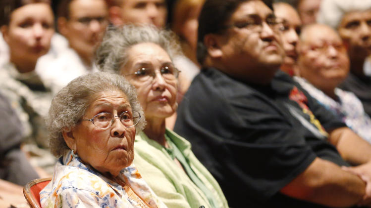 Irene Permansu Lane, left, the widow Comanche Code Talker Melvin Permansu, watches a video presentation during a ceremony honoring the code talkers presented by the Comanche National Museum and Cultural Center, in Lawton, Okla, Thursday, Sept. 26, 2013. (AP Photo/Sue Ogrocki)