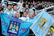 Manchester City&#39;s supporters celebrate after their team&#39;s 3-2 victory over Queens Park Rangers. Manchester City won the game 3-2 to secure their first title since 1968