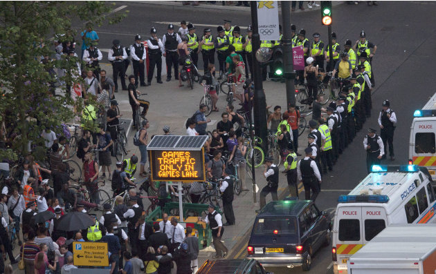 Police surround part of a group of protesting cyclists who tried to block traffic with a mass cycle ride on a road outside the Olympic Park during the Opening Ceremony of the 2012 Summer Olympics, Fri