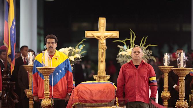 In this photo released by Miraflores Press Office, Venezuela's interim President Nicolas Maduro, left,  and Diosdado Cabello, President of Venezuela's National Assembly stand next to the flag-draped coffin containing the body of Venezuela's late President Hugo Chavez on display during his wake at a military academy where his body will lie in state until his funeral in in state in Caracas, Venezuela, Wednesday, March 6, 2013. Seven days of mourning were declared, all schools were suspended for the week and friendly heads of state were expected for an elaborate funeral Friday. (AP Photo/Miraflores Presidential Press Office)