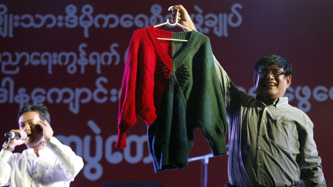 In this Thursday, Dec. 27, 2012 photo, presenters show a hand-knit woolen sweater, made by Myanmar opposition leader Aung San Suu kyi, during an auction at a fundraising concert to mark the 2nd anniversary of her National League for Democracy Party's education network, at Peoples Square in Yangon, Myanmar. The sweater was sold at an auction in Myanmar for almost $50,000. (AP Photo/Khin Maung Win)