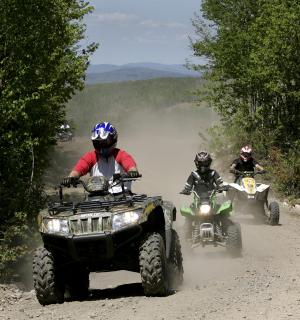 """FILE -  In this Sunday, May 23, 2010 file photo, Jude Stohl leads Leigha Cicchetto and his son Ethan Stohl on a ride through Jericho Park's trail system in Berlin, N.H. In New Hampshire, a new interconnected all-terrain vehicle trail system dubbed """"Ride the Wilds"""" will officially open June 15, 2013, capping years of work by more than a dozen off-road vehicle clubs who worked with state agencies and local communities to link 1,000 miles of trails across Coos County. (AP Photo/Jim Cole, File)"""