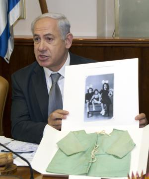Israeli Prime Minister Benjamin Netanyahu shows an item dedicated to the Yad Vashem Holocaust memorial as part of their campaign called 'Gathering the Fragments' as he chairs a cabinet meeting in his Jerusalem offices a day before Israel begins it annual Holocaust Memorial Day, Tuesday, April 17, 2012.  Netanyahu shows a family photo and a shirt worn by Refael Denty, a four-year-old Jewish boy from Athens, Greece, who perished in the Auschwitz death camp. The shirt was donated by Refael's sister, Nina Abayov, one of the only survivors from her entire family, whose aunt returned to the family home after the war and rescued any possessions that had not been looted: linens and clothes, including the shirt belonging to little Refael.(AP Photo/Jim Hollander, Pool)