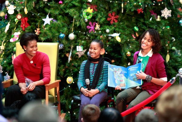 First lady Michelle Obama and her daughters Sasha (C) and Malia read Christmas stories to children at the Children's National Medical Center on December 22, 2009 in Washington, DC. The first lady tour