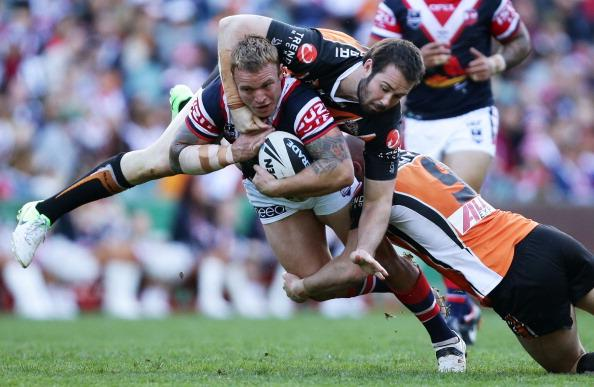 Jake Friend of the Roosters is tackled over the top by Aaron Woods of the Tigers during the round 25 NRL match between the Sydney Roosters and the Wests Tigers at Allianz Stadium on August 26, 2012 in