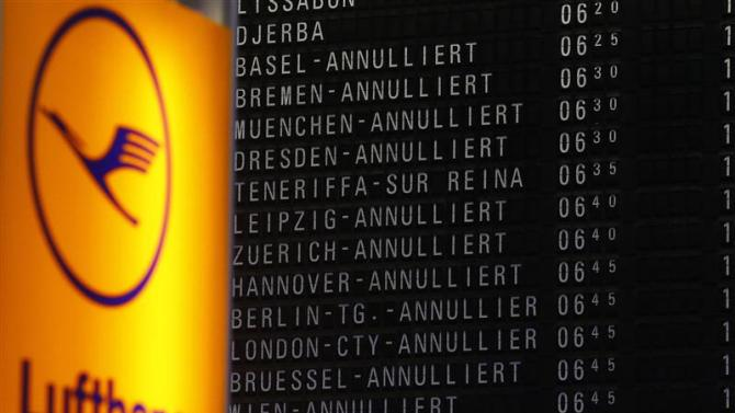 File photo of cancelled flights on a flight schedule board next to the logo of German air carrier Lufthansa at Fraport airport in Frankfurt