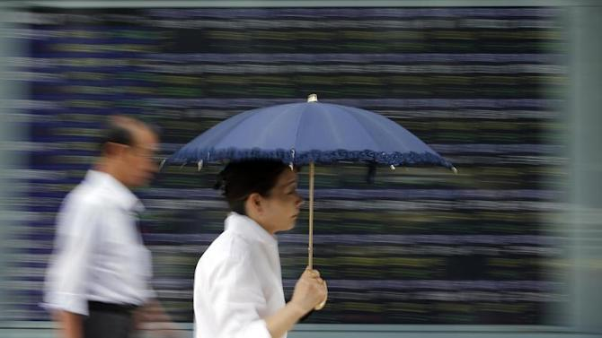 A woman holding a parasol walks past a stock quotation board outside a brokerage in Tokyo