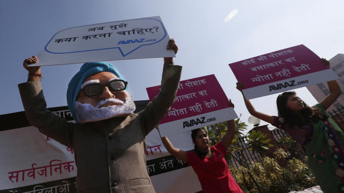 """A man wearing a mask of Indian Prime Minister Manmohan Singh, left, participates in a protest along with women outside the court where the accused in a gang rape of a 23-year-old woman will be tried, in New Delhi, India, Monday, Jan. 21, 2013. Legal proceedings in the fatal gang-rape attack on a student in India's capital were set to begin Monday in a fast-track court for crimes against women that has stirred debate over how best to deliver justice to rape victims. Placard on left reads: """"What should I do?"""" (AP Photo/Saurabh Das)"""