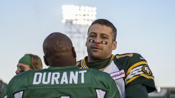 Saskatchewan Roughriders quarterback Darian Durant hugs Edmonton Eskimos quarterback Mike Reilly at the end of their CFL football game in Regina, Saskatchewan