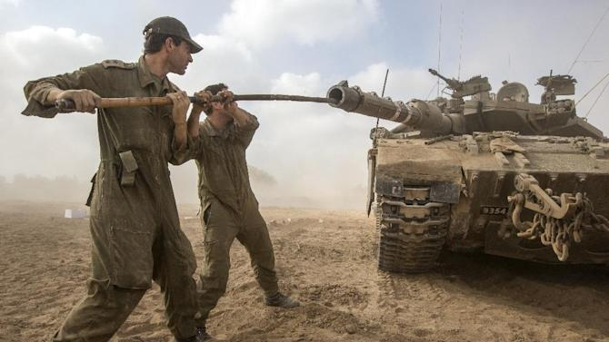 Israeli soldiers work on their Merkava tank at an army deployment area near Israel's border with the Gaza Strip, on July 24, 2014