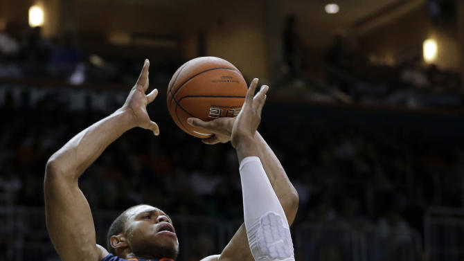 Miami's Kenny Kadji (35) is unable to block Virginia's Justin Anderson (23) during the first half of an NCAA college basketball game in Coral Gables, Fla., Tuesday, Feb. 19, 2013. (AP Photo/J Pat Carter)