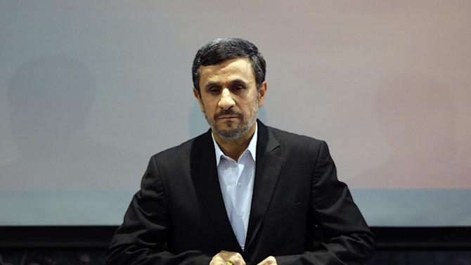 """Iranian President Mahmoud Ahmadinejad adjusts his jacket as he listens to the Iranian national anthem at the start of a press conference in Tehran, Iran, Tuesday, Oct. 2, 2012. Ahmadinejad blamed the steep drop in Iran's currency Tuesday to """"psychological pressures"""" linked to Western sanctions over Tehran's nuclear program. The remarks were part of his attempt to deflect criticism from political rivals that his government's policies also have contributed to the nosedive of the Iranian rial, which has lost more than half its value against the U.S. dollar this year and has sharply pushed up costs for many imported goods. (AP Photo/Vahid Salemi)"""