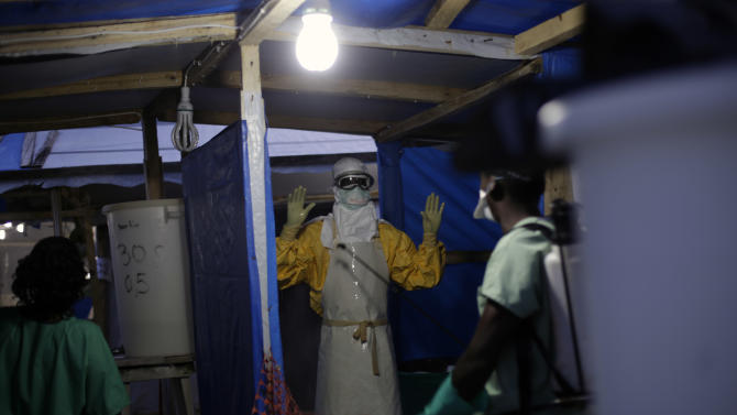 FILE- In this Thursday, Nov. 20, 2014 file photo, an MSF Ebola heath worker is sprayed as he leaves the contaminated zone at the Ebola treatment centre in  Gueckedou, Guinea.  The operation to fight Ebola in West Africa has hampered the campaigns against malaria, a preventable and treatable disease that is claiming many thousands of lives. In information released Sunday Dec. 28, 2014,  Dr. Bernard Nahlen, deputy director of the U.S. President's Malaria Initiative says they have had to stop pricking fingers to do blood tests for malaria, so statistics show a decrease in reported cases of maleria but the decrease is likely because people are too scared to go to health facilities and are not getting treated for malaria. (AP Photo/Jerome Delay, FILE)