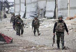 Forces loyal to President al-Assad walk with weapons in Aleppo town of Naqaren