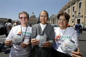 "Nuns Bottani, Castalone and Sammut hold the logo of an international campaign called ""Play in Favour of Life-Denounce Human Trafficking,"" on the risks they say will be associated with the June-July games, as they pose in front of Saint Peter's basilica in"