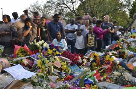 Mourners offer flowers for the late former President Nelson Mandela outside his home in Houghton, Johannesburg