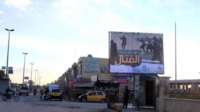 People walk under a billboard erected by the Islamic State group in Raqa on November 2, 2014