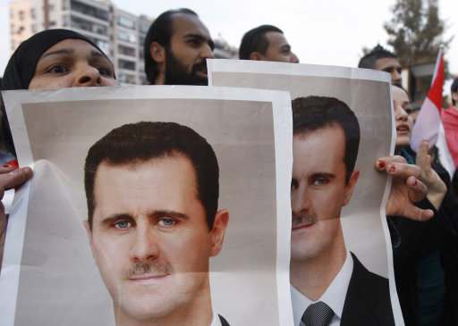 A pro-Syrian regime protester shouts slogans as she holds portraits of Syrian president Bashar Assad, during a protest in front the Iranian embassy to thank Iran for their support of the Syrian regime, in Damascus, Syria, Thursday Nov. 24, 2011. An Arab League committee has given Syria 24 hours to agree to allow an observer mission into the country or it could face sanctions.  (AP Photo/Muzaffar Salman)