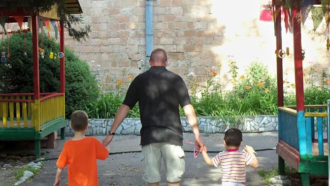 "In this June 17, 2012 photo provided by the Fenske family, Kevin Fenske, center, walks with his son Esen, 6, left, who was adopted from Kyrgyzstan in 2007, and Kamilia, right, whom the Fenskes have been trying to adopt since she was an infant, during a visit to Kamilia in Bishkek, Kyrgyzstan. The Fenskes have four other adopted children, but even with a bustling household, there's no thought about dropping the quest to adopt Kamila, whom they've visited only this one time. ""She's our daughter - it's that simple,"" Shannon Fenske said. ""We promised her a family. We will not stop fighting for her until she's here, where we feel she belongs."" (AP Photo/the Fenske family, Shannon Fenske)"
