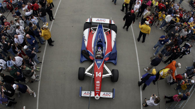 In this image made with a fisheye lens, the car of Takuma Sato, of Japan, is towed from the garage area to pit lane before the start of the Indianapolis 500 auto race at the Indianapolis Motor Speedway in Indianapolis, Sunday, May 26, 2013. (AP Photo/Darron Cummings)