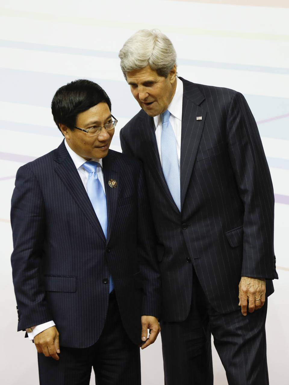 U.S. Secretary of State John Kerry, right, chats with Vietnam's Foreign Minister Pham Binh Minh during a group photo session at the 3rd East Asia Summit (EAS) Foreign Ministers' Meeting in Bandar Seri Begawan, Brunei, Tuesday, July 2, 2013. (AP Photo/Vincent Thian)