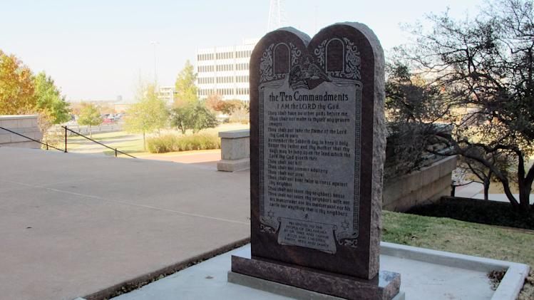 FILE - In this Friday, Nov. 16, 2012, file photo, a Ten Commandments monument erected outside the Oklahoma state Capitol is shown in Oklahoma City. After hearing from satanists, Hindus and an animal rights group, the panel that oversees the grounds at the Oklahoma Capitol says it's not taking any more requests for new displays at the Statehouse. The Oklahoma Capitol Preservation Commission voted Thursday, Dec. 19, 2013, to approve the ban until a court dispute over the current Ten Commandments monument is settled. It was that monument that the New York-based Satanic Temple said opened the door for it to seek its own display at the Statehouse in Oklahoma City. (AP Photo/Sean Murphy, File)