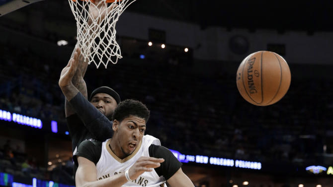 New Orleans Pelicans forward Anthony Davis (23) ands Sacramento Kings center DeMarcus Cousins (15) watch the ball head away during the first half of an NBA basketball game in New Orleans, Friday, March 27, 2015. (AP Photo/Bill Haber)