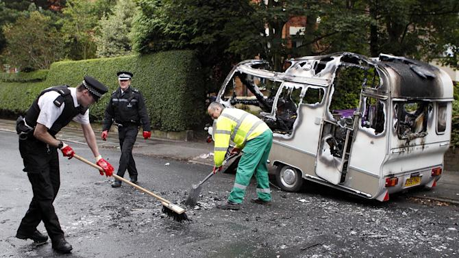 Merseyside Police officers help clean up a burnt out caravan in  the Toxteth area of Liverpool, England Wednesday Aug. 10, 2011 following  rioting in the area Tuesday night. Thousands of extra police officers flooded into London  in a bid to end Britain's worst rioting in a generation. An eerie calm prevailed in the capital, but unrest spread across England on a fourth night of violence driven by diverse and brazen crowds of young people (AP Photo/Peter Byrne/PA) UNITED KINGDOM OUT