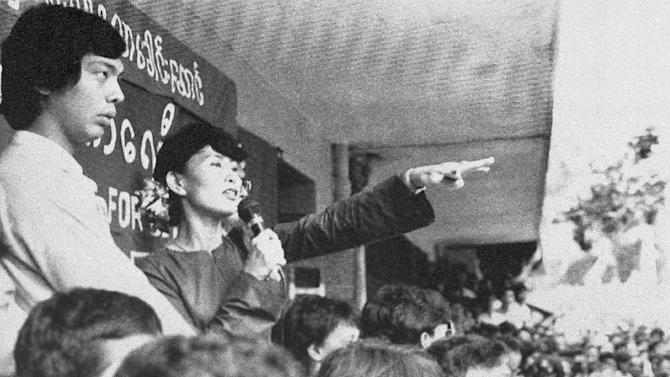FILE - In this Oct. 14, 1991 file photo, Burma's main opposition leader Aung San Suu Kyi gestures while addressing thousands at a rally in Rangoon, Burma. Twenty-four years ago Aung San Suu Kyi left Europe for what was then a military-controlled nation called Burma. She returns Wednesday, June 13, 2012 the icon of Myanmar's democracy movement to a continent eager to hear from her whether the country's recent reforms truly spell the end of its cruel dictatorship. (AP Photo/The Nation, File)