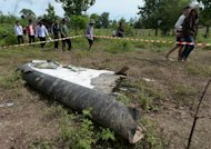 People walk past pieces of a Lao Airlines plane after it crashed into the Mekong river near Pakse town, on October 17, 2013