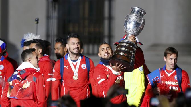 Chile's Arturo Vidal holds the trophy ourside the La Moneda presidential palace  after Chile defeated Argentina to win the Copa America 2015 final soccer match in Santiago