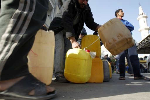 Palestinians wait in a queue to fill containers with fuel at a petrol station in Gaza City