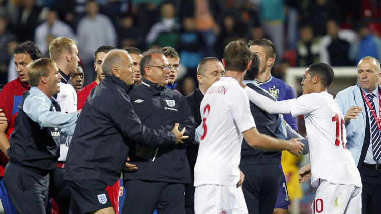 Serbian players, in red shirts, clash with England players, during their 2013  European Under-21 Championship play-off, Second leg match, in Krusevac, Serbia, Tuesday, Oct .16, 2012. England Under-21s claimed their place at Euro 2013 amid unsavoury scenes during their qualifying play-off in Serbia. Players appeared to be pelted with missiles after Connor Wickham struck in injury time of the second leg to book England's trip to next summer's finals in Israel. (AP Photo/Miroslav Todorovic)