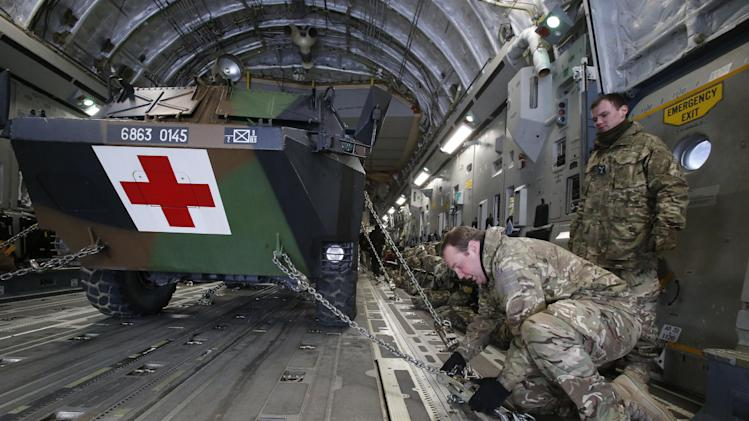 A British military personnel fix a French army medical armoured personnel carrier inside a British C17 transport plane prior to take off at army base in Evreux, 90 kms (56 mls) north of Paris, Monday, Jan. 14, 2013. British military equipment was readied for deployment in Mali on Monday as international intervention in the country increased following advances in the north by Islamic extremists with reported links to Al-Qaida. Two C-17 transport planes have arrived at the French military airbase at Evreux, bound for Mali. Two C-17 transport planes have arrived at the French military airbase at Evreux, bound for Mali. (AP Photo/Michel Euler)