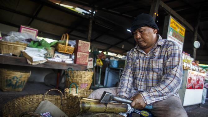A vendor uses an ax to crack a bamboo cylinder which has a baked sticky rice dish called Khao Lam, at a shop in Chonburi