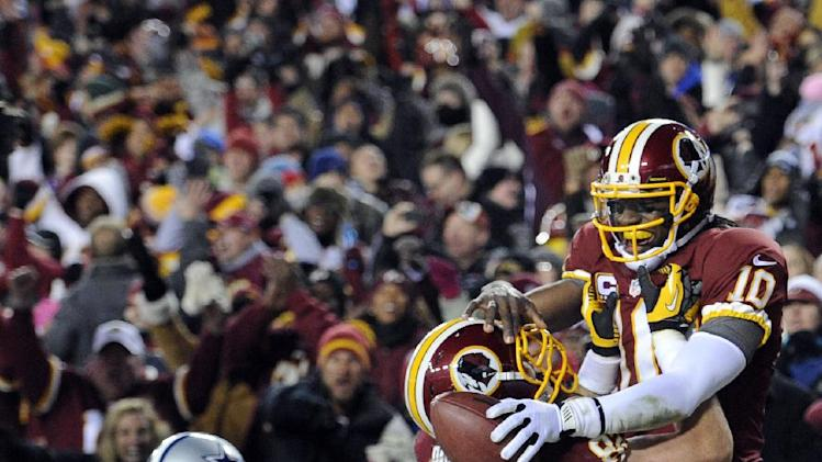 Washington Redskins quarterback Robert Griffin III (10) celebrates his touchdown with tight end Logan Paulsen (82) during the second half of an NFL football game against the Dallas Cowboys Sunday, Dec. 30, 2012, in Landover, Md. (AP Photo/Nick Wass)