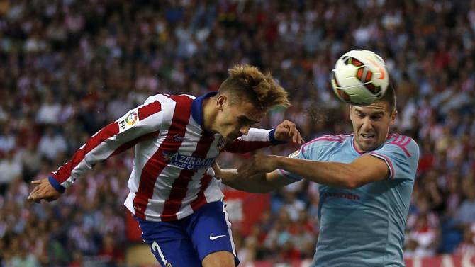 Atletico Madrid's Antoine Griezmann jumps for the ball with Celta Vigo's Andreu Fontas during their Spanish first division soccer match at Vicente Calderon stadium in Madrid