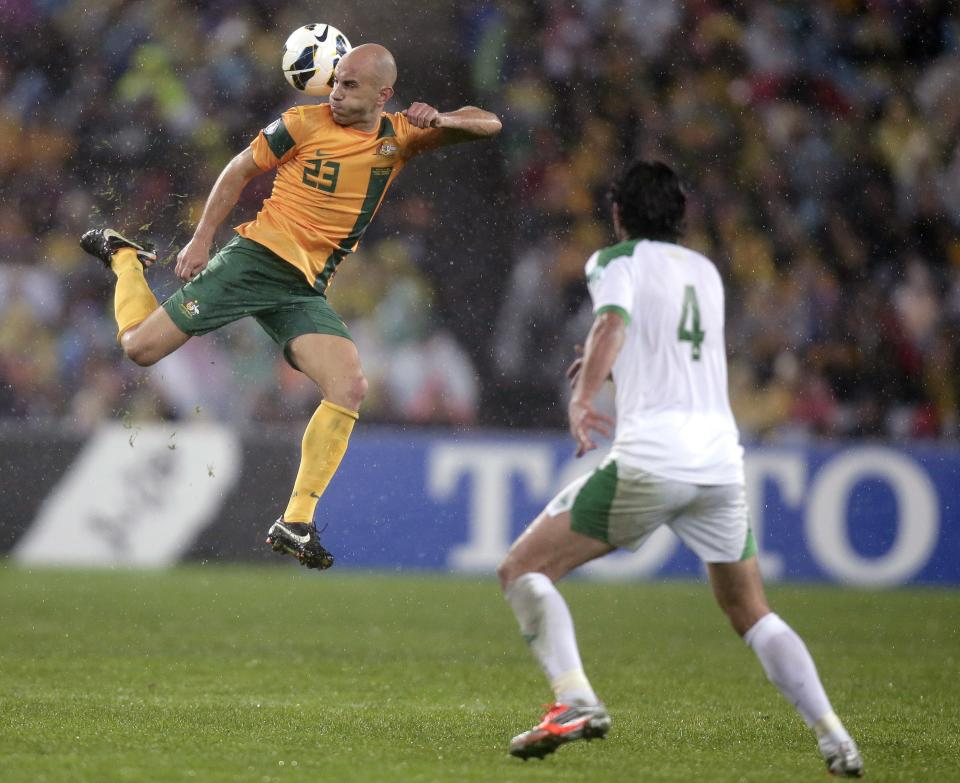 Australia's Mark Bresciano, left, kicks the ball behind his back during their World Cup soccer Asian qualifying match against Iraq at the Sydney Olympic Stadium in Sydney, Australia, Tuesday, June 18, 2013. Australia won the match 1-0 and qualify for the 2014 World Cup in Brazil. (AP Photo/Rick Rycroft)