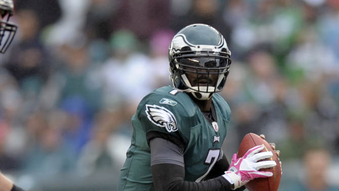 Philadelphia Eagles quarterback Michael Vick (7) looks to pass as San Francisco 49ers linebacker Aldon Smith (99) hangs on to his leg in the first half of an NFL football game Sunday, Oct. 2, 2011 in Philadelphia. Vick was able to get the pass off. (AP Photo/Michael Perez)