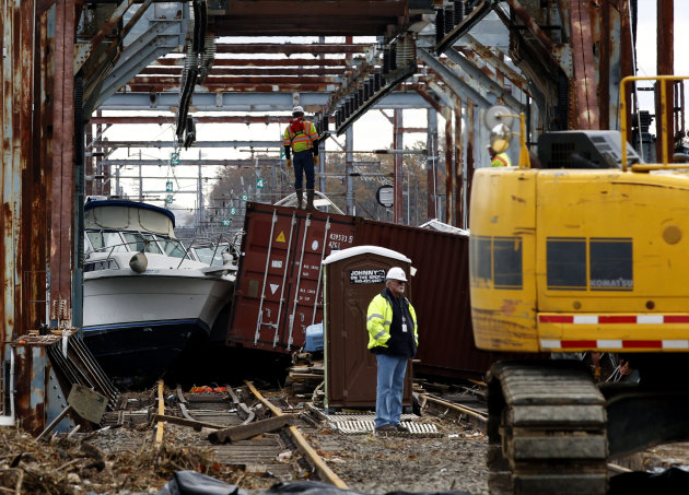 Workers try to clear boats and debris from the New Jersey Transit Morgan draw bridge Wednesday, Oct. 31, 2012, in South Amboy, N.J., after Monday&#39;s storm surge from Sandy pushed boats and cargo containers onto the train tracks. Travel in the Northeast creaked back into motion on Wednesday, a grinding, patchy recovery that made it clear that stranded travelers will struggle to get around for days to come. (AP Photo/Mel Evans)(AP Photo/Mel Evans)