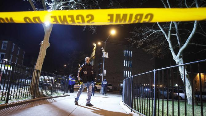 A police officer puts up crime scene tape at scene of shooting where two New York Police officers were shot dead in Brooklyn borough of New York