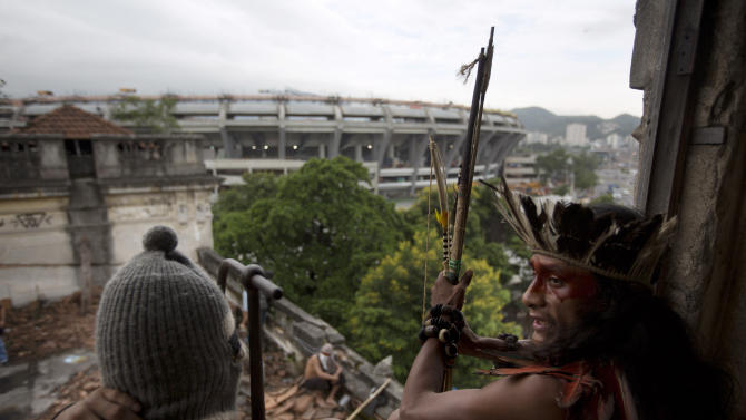 A man wearing a headdress and another wearing a ski mask sit on a windowsill on the site of an old Indian museum, in Rio de Janeiro, Brazil, Saturday, Jan. 12, 2013. Police in riot gear on Saturday surrounded the site, now an indigenous settlement of men and women living in 10 homes, and prepared to enforce their eviction. The settlement is next to the Maracana stadium, pictured in background, which is being refurbished to host the opening and closing ceremonies of the 2016 Olympics and the final match of the 2014 World Cup. The streets around the stadium will also undergo a vast transformation as part of the area's transformation into a shopping and sports entertainment hub. (AP Photo/Felipe Dana)