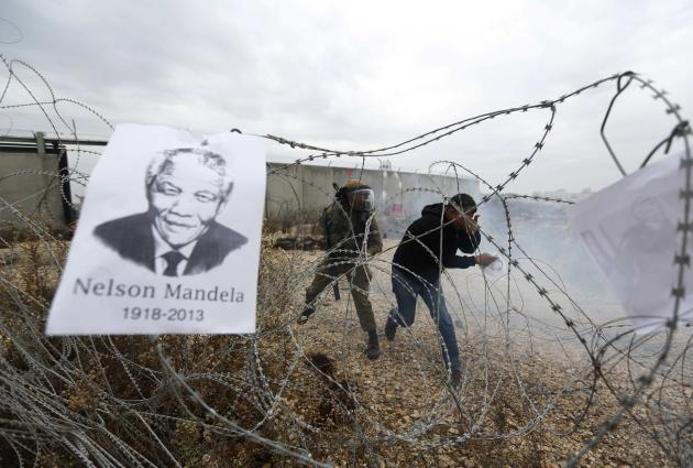 A placard depicting former South African President Nelson Mandela hangs on a barbed wire during clashes at a weekly demonstration against Jewish settlements in the West Bank village of Bilin