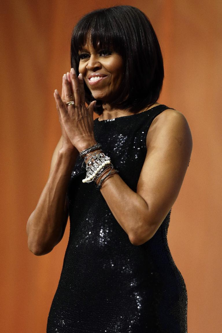 First lady Michelle Obama acknowledges the crowd as President Obama speaks to supporters and donors at an inaugural reception for the 57th Presidential Inauguration at The National Building Museum in Washington, Sunday, Jan. 20, 2013. (AP Photo/Charles Dharapak)