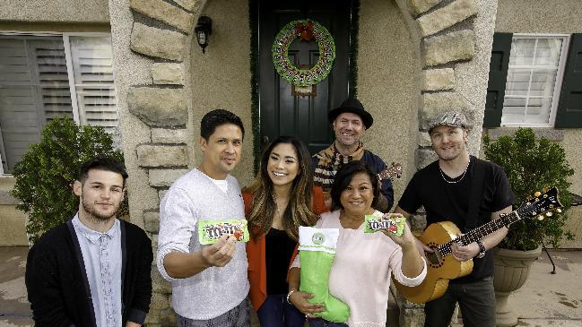 IMAGE DISTRIBUTED FOR MARS CHOCOLATE NOTH AMERICA - Jessica Sanchez, celebrated singer and finalist on American Idol Season 11, shares some of the first bags of M&M'S® Crispy with fans on Dec. 18, 2014 in her hometown of Chula Vista, Calif. Sanchez surprised fans outside their homes with holiday carols and delivered M&M'S® Crispy in festive stockings and wreaths. The product is returning to store shelves this month after a 10-year hiatus thanks to a vocal fan base who pleaded for its return. (Photo by Christy Radecic/Invision for Mars Chocolate North America/AP Images)