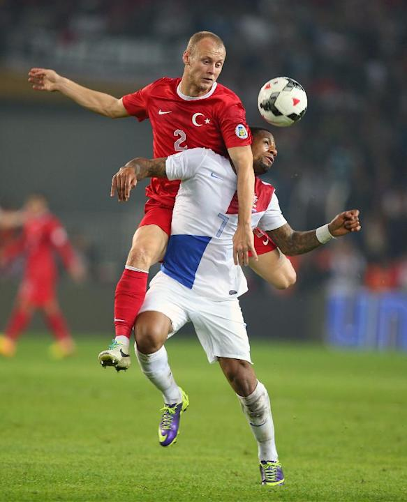Turkey's Semih Kaya, top, and Jeremain Lens of Netherlands fight for the ball during their World Cup Group D qualifying soccer match at Sukru Saracoglu Stadium in Istanbul, Turkey,  Tuesday, Oct. 15,