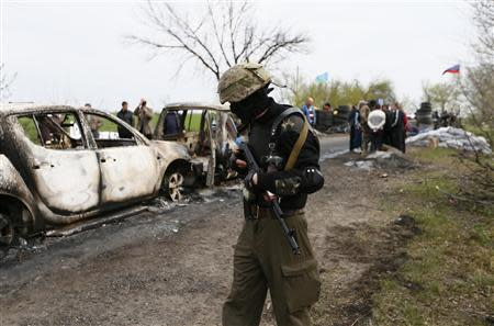 Pro-Russian militant walks near a checkpoint which was the scene of a gunfight overnight near the city of Slaviansk