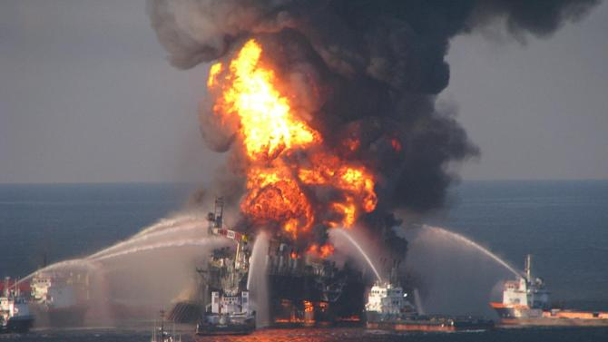 """FILE- In this April 21, 2010 file image provided by the U.S. Coast Guard, fire boat response crews battle the blazing remnants of the off shore oil rig Deepwater Horizon. The Obama administration put a temporary stop to new federal contracts with British oil company BP on Wednesday, citing the company's """"lack of business integrity"""" and criminal proceedings stemming from the Deepwater Horizon disaster in 2010.  (AP Photo/US Coast Guard, File)"""